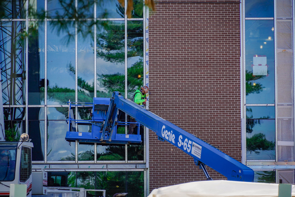 Photo of worker working on brick exterior of STEM facility