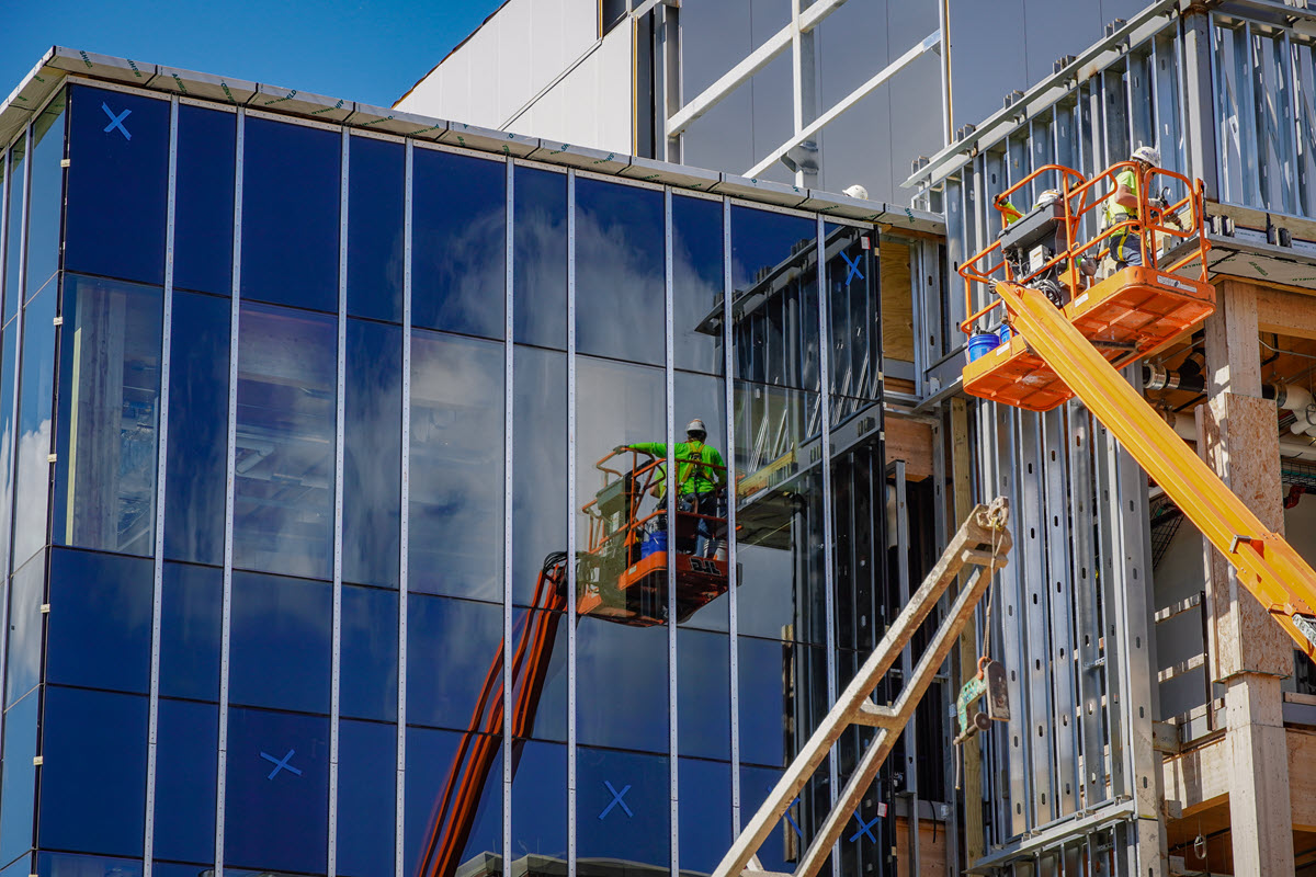 Construction workers working on glass wall section of STEM facility