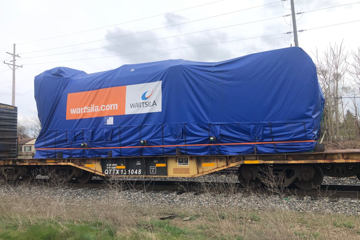 Photo of rail car bringing one of three reciprocating internal combustion engines to the power plant site