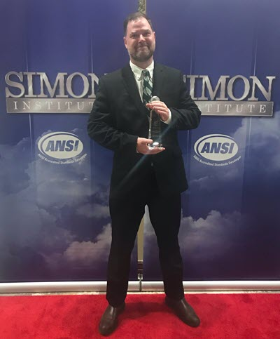 Photo of Josh Sego holding his trainer of the year award at the Simon Institute event